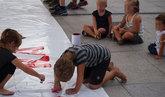 Dos niños pintan una pancarta mientras otros tres les observan en la...