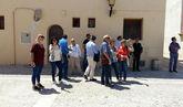 Turistas observan los edificios en una visita en un pueblo de...