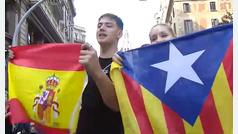 Dos jóvenes con diferentes banderas se abrazan y piden respeto en Barcelona