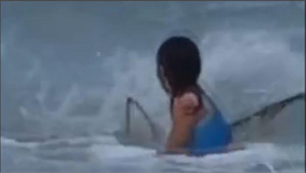 Un tiburón acecha a una niña en una playa mientras su madre lo graba