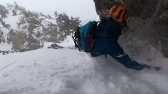 Un snowboarder se agarra a las rocas para evitar ser engullido por una avalancha