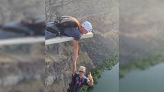 Se cuelga en el vacío sujetado por una mano en un salto BASE de alto riesgo