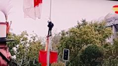 Un paracaidista se queda enganchado a una farola en el desfile del Día de la Hispanidad