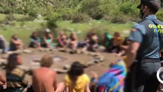 Los integrantes del campamento de la 'Familia Arcoíris' intentan abrazar desnudos a los guardias que